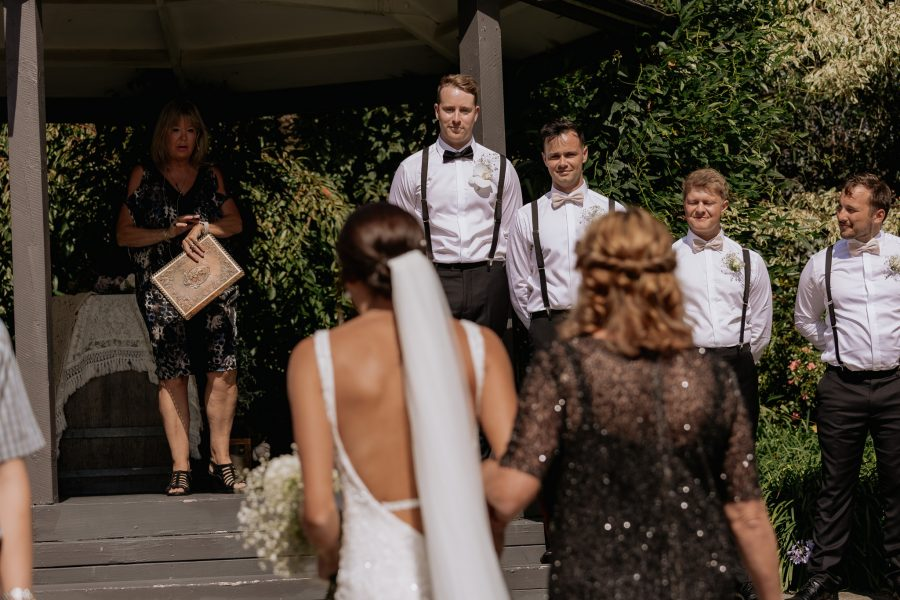 Groom watches bride walk towards him