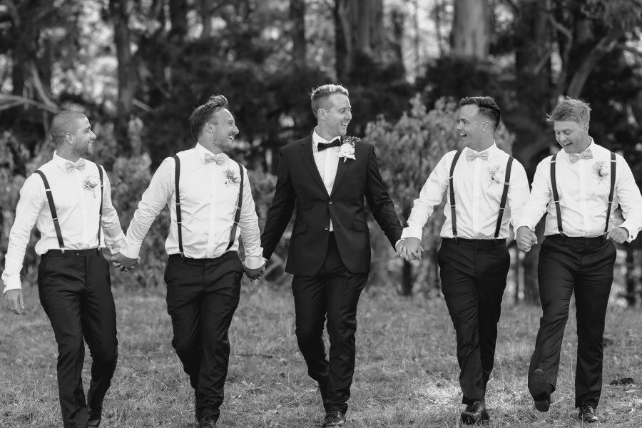 Groomsmen walking holding hands laughter