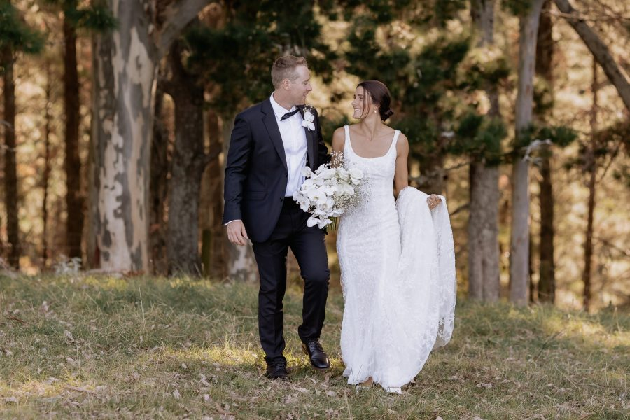 Wedding couple walking in country field