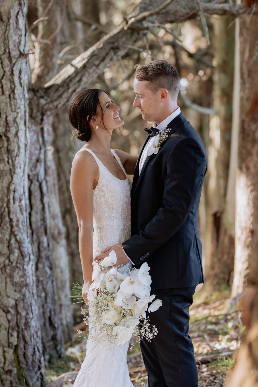 Bridal couple looking at each other in tree tunnel