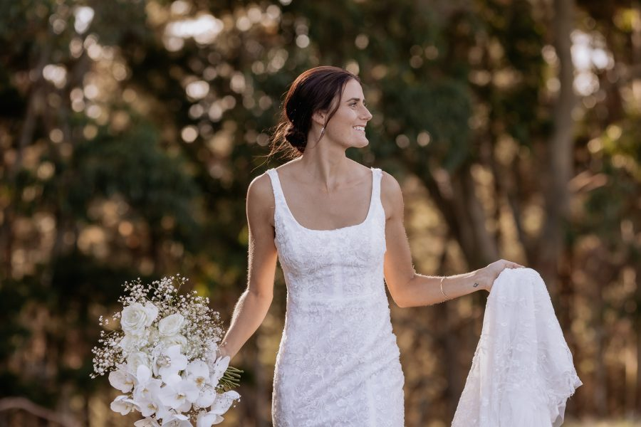 Country bride in lace dress walking holding veil