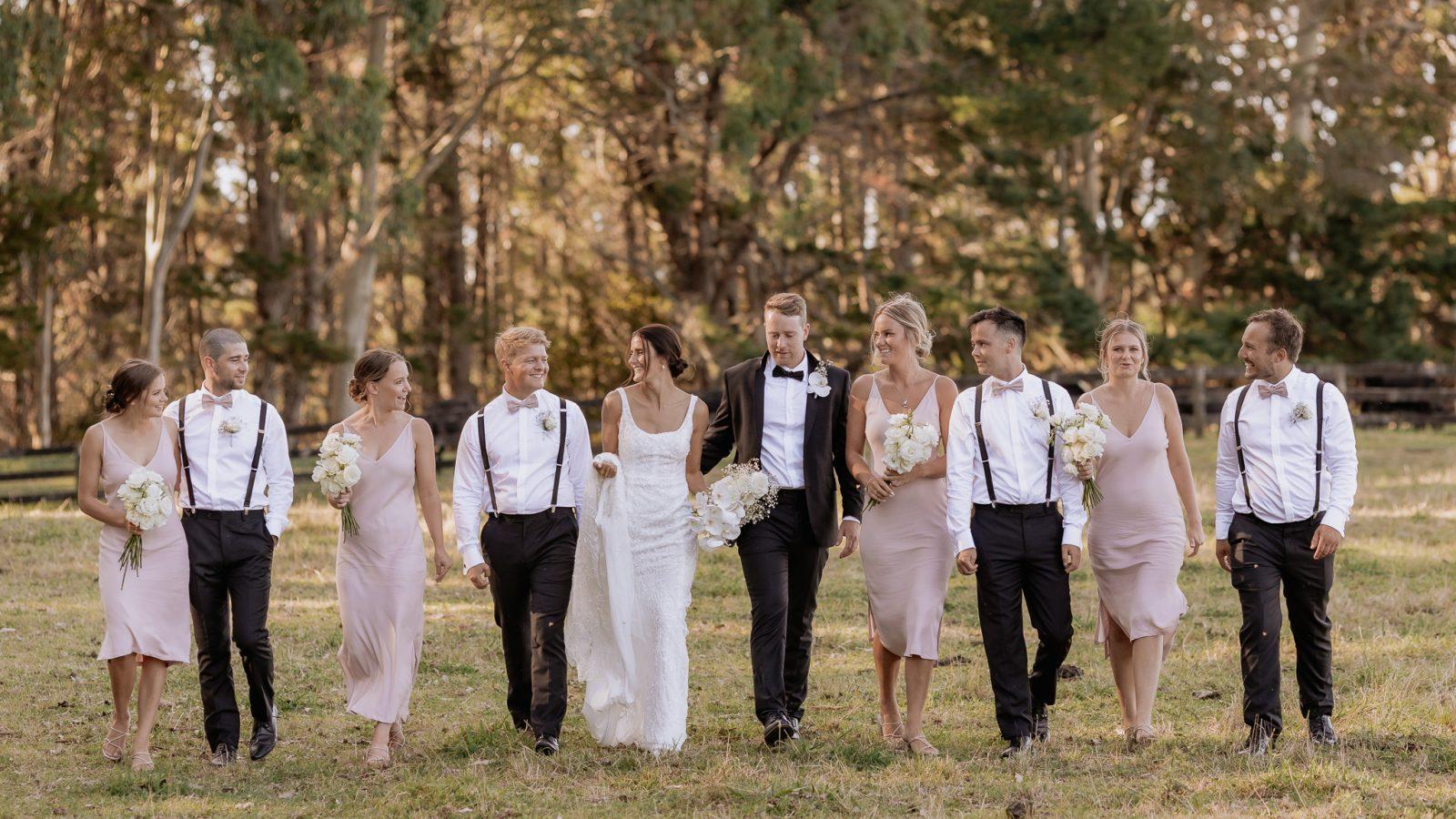 Pink Wedding party walking in field having fun
