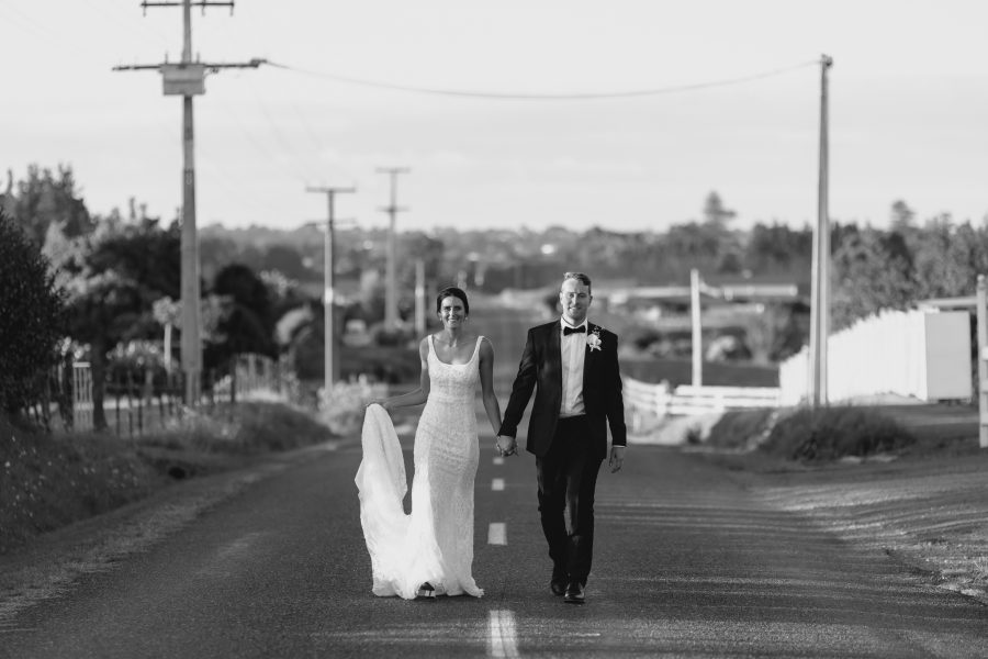 Bride and groom walking up country road in black and white