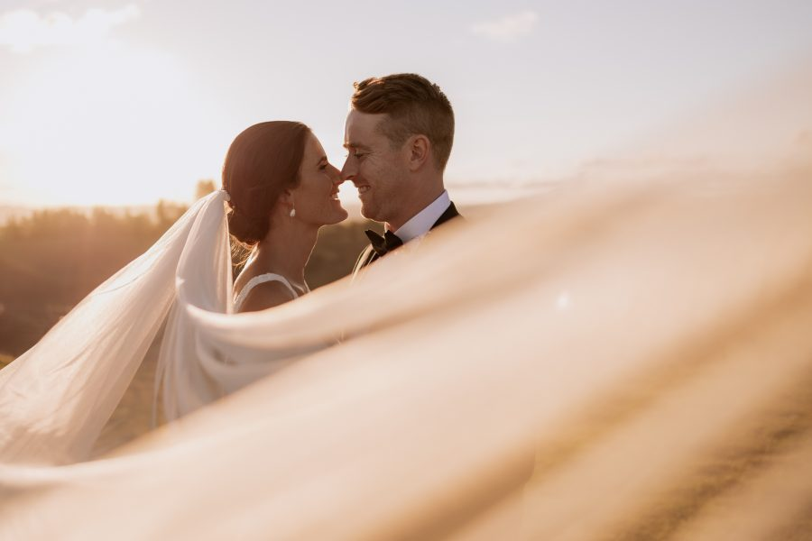Couple with veil wrapped around them