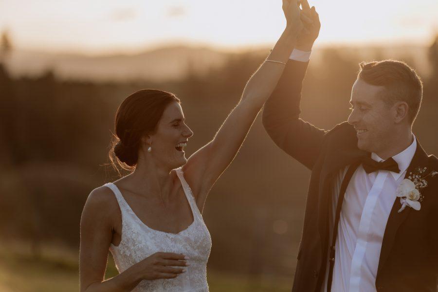 Bride and groom dancing in the field