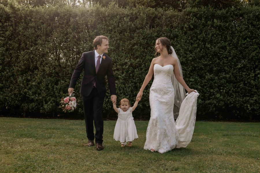 Bride and groom walking holding hands with flower girl