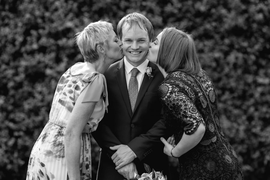 Mother of groom and sister kissing groom