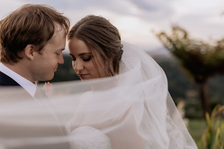 bride and groom under windy veil