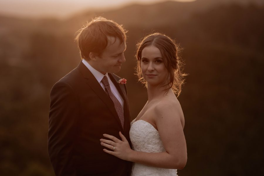 beautiful bride stares at camera with her husband looking at her