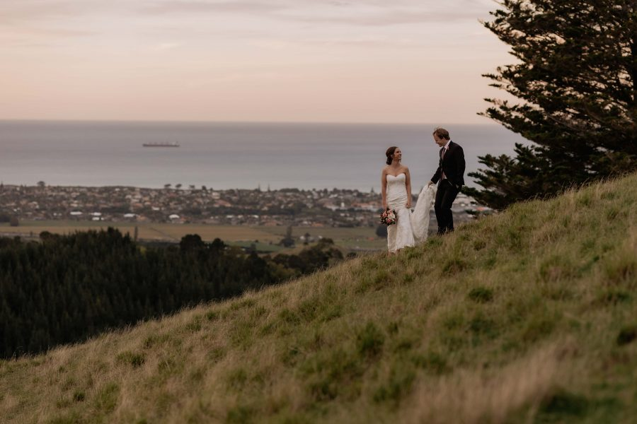 Bride and groom walking high on hills with ocean behind them