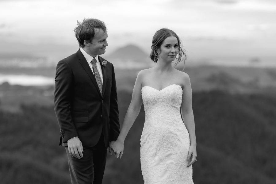 Cheeky natural bride with her husband with Mount Maunganui in New Zealand behind them