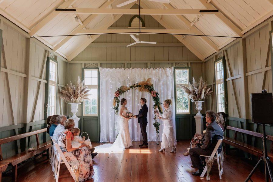 Wedding ceremony in progress under arch