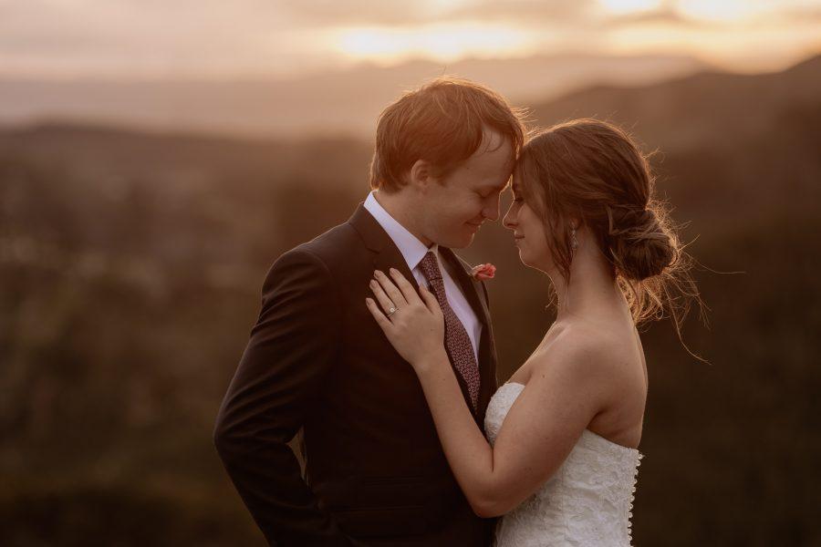 Cuddling bridal couple in golden light