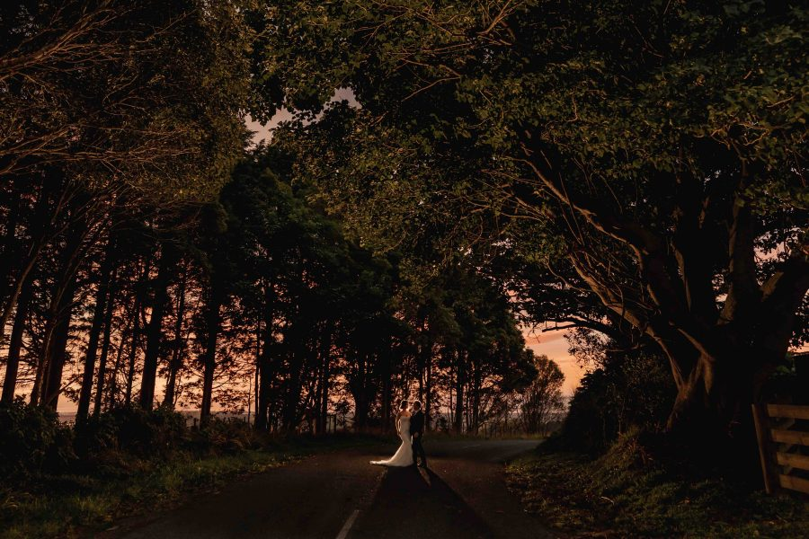 Photo of bride and groom on road with trees lit up at sunset