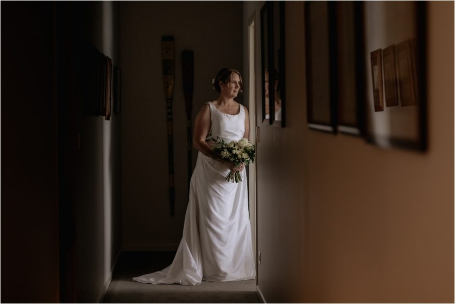 Bride in door way during portraits at Quail Lodge accommodation in Auckland