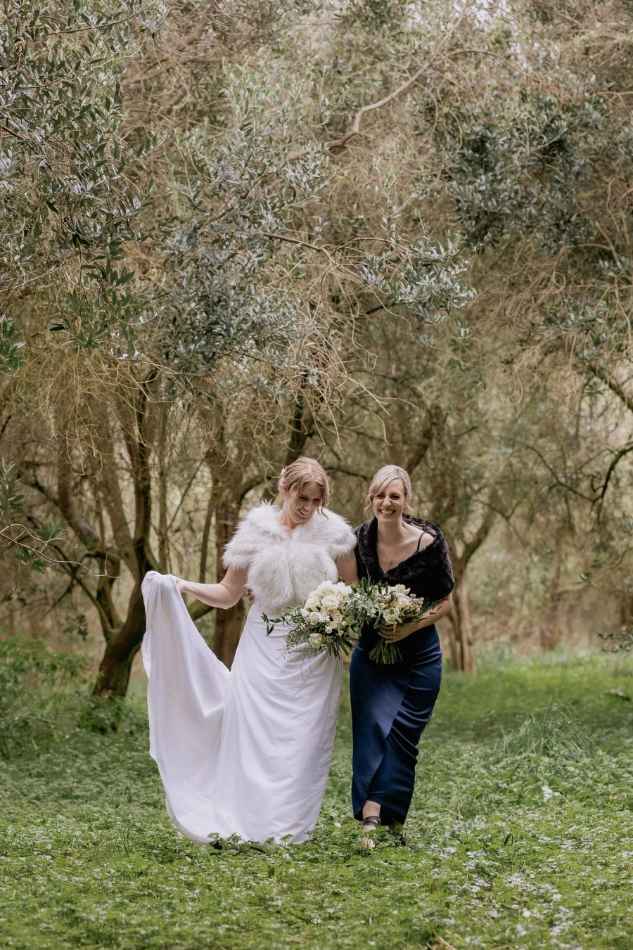 bride and bridesmaid in Olive grove at Bracu laughing