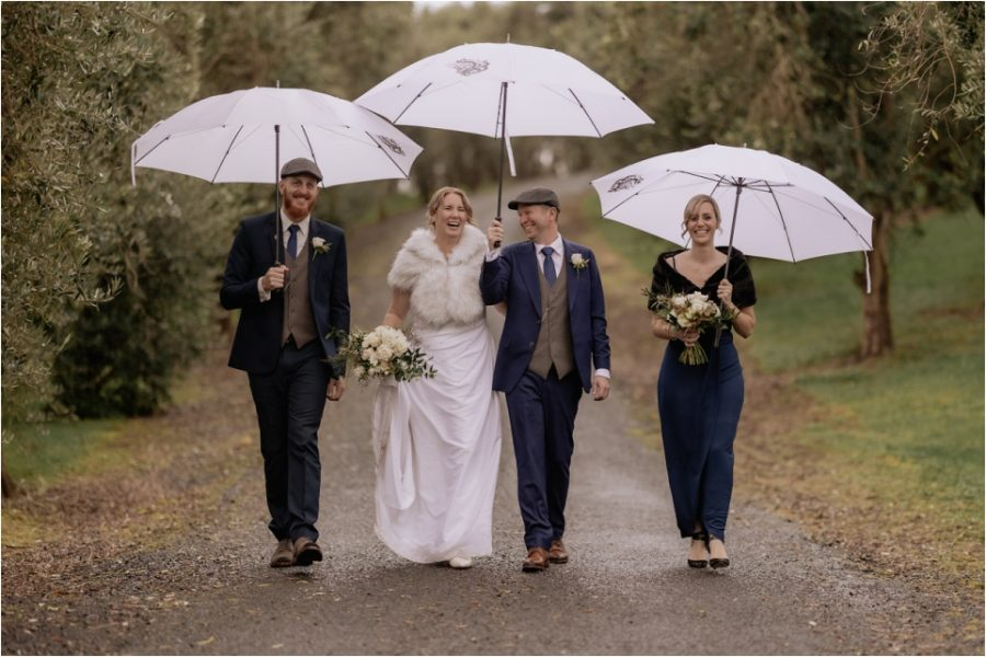 bridal party walking in the rain with umbrellas at Bracu New Zealand