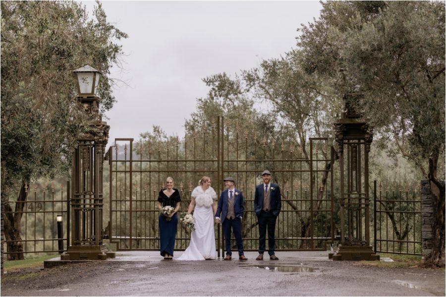 Bracu gates with wedding party on wet day