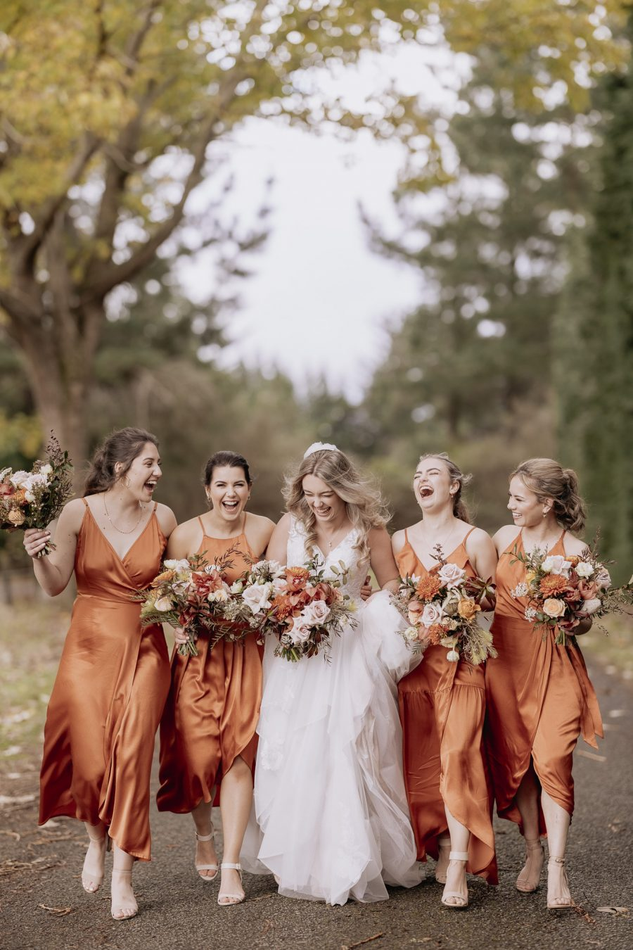 laughing happy bride with bridal squad girls in rust dresses