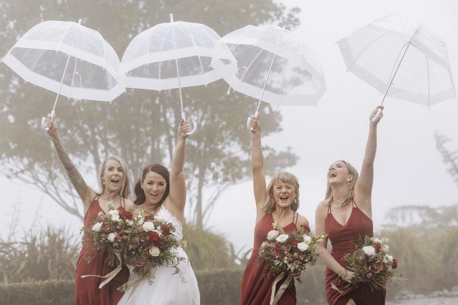 Bride with bridesmaids laughing in the rain umbrellas