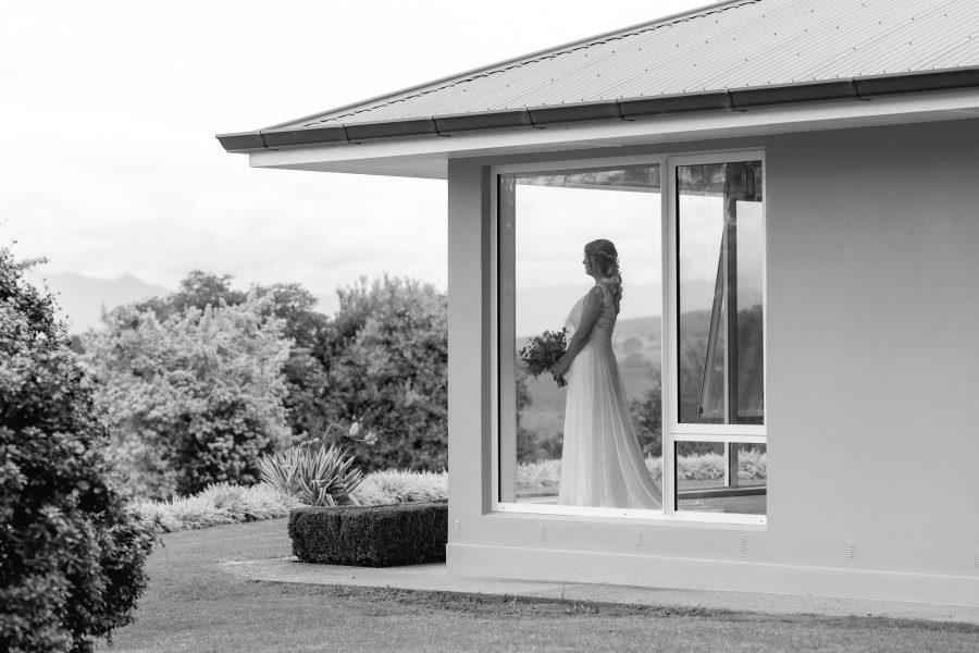 Bride in window of farm house overlooking ceremony area