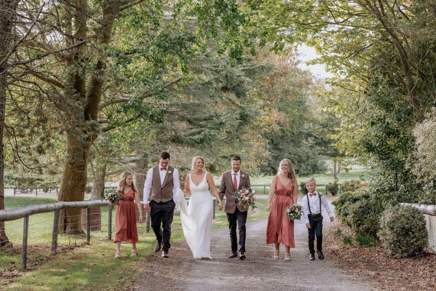 wedding party walking on country driveway in waikato in coral dresses