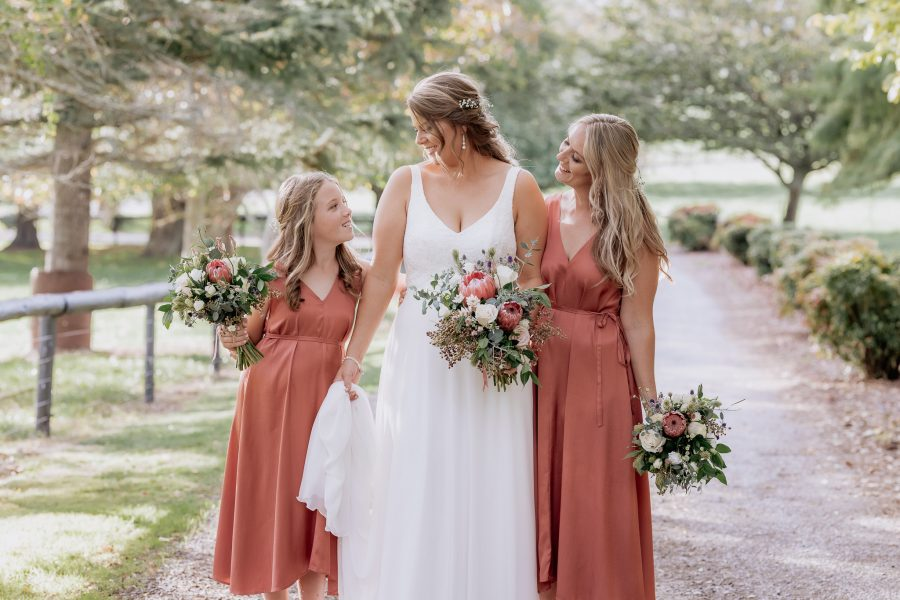 bride with bridesmaid and flower girl in rust coral dresses