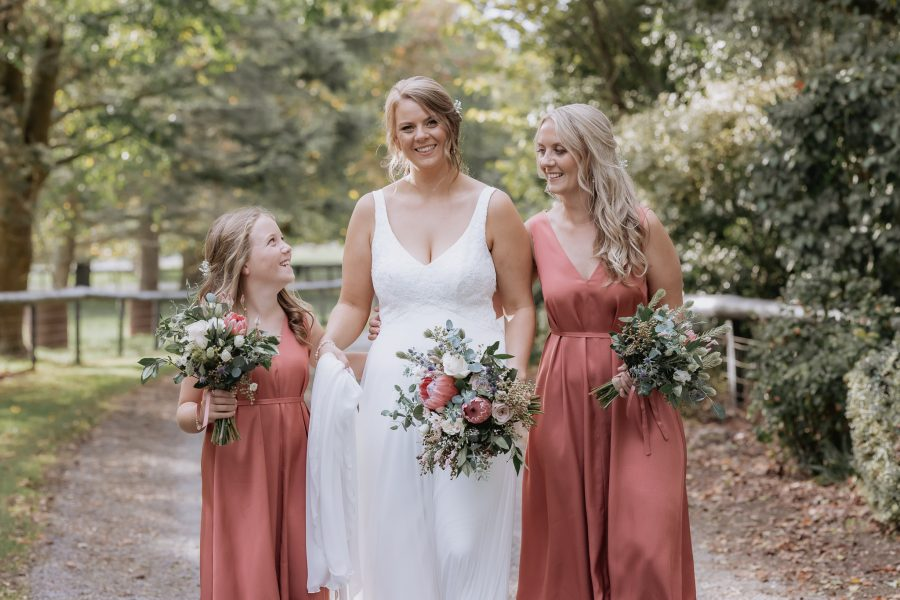 Happy country bride her girls in blush pink dresses
