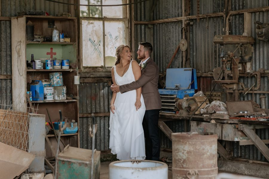 wedding photos in the farm shed bride looking laughing at her groom