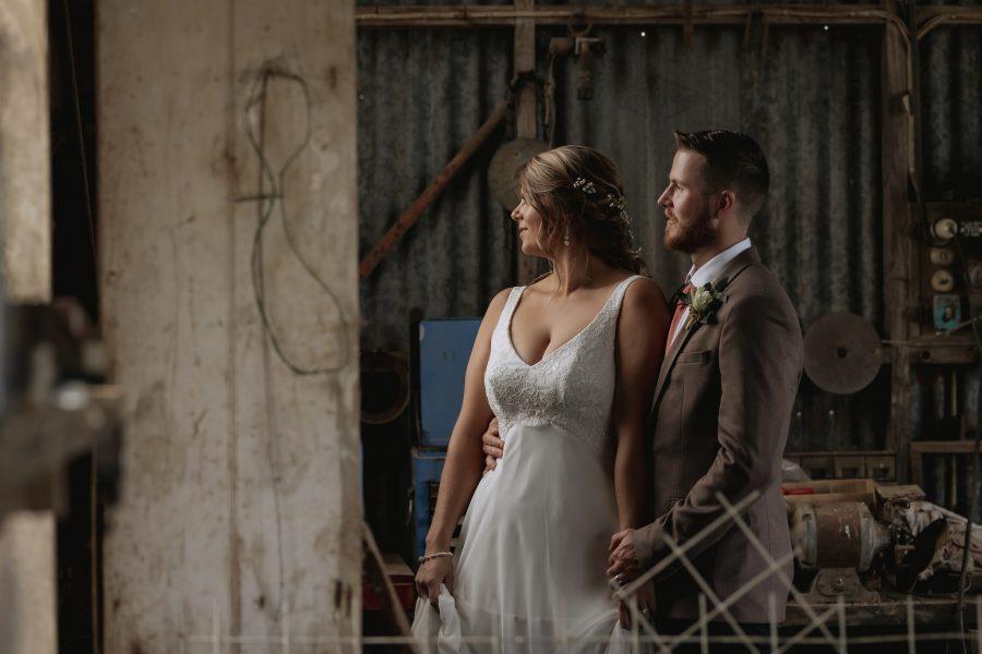 wedding portrait of bride and groom in door way of rustic shed