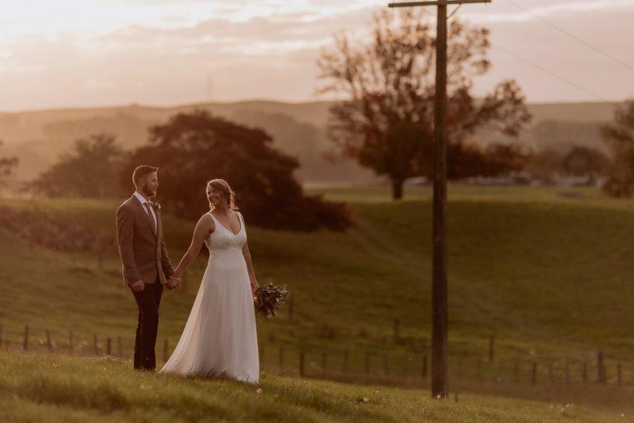 Bride and groom walking over farm at waikato wedding