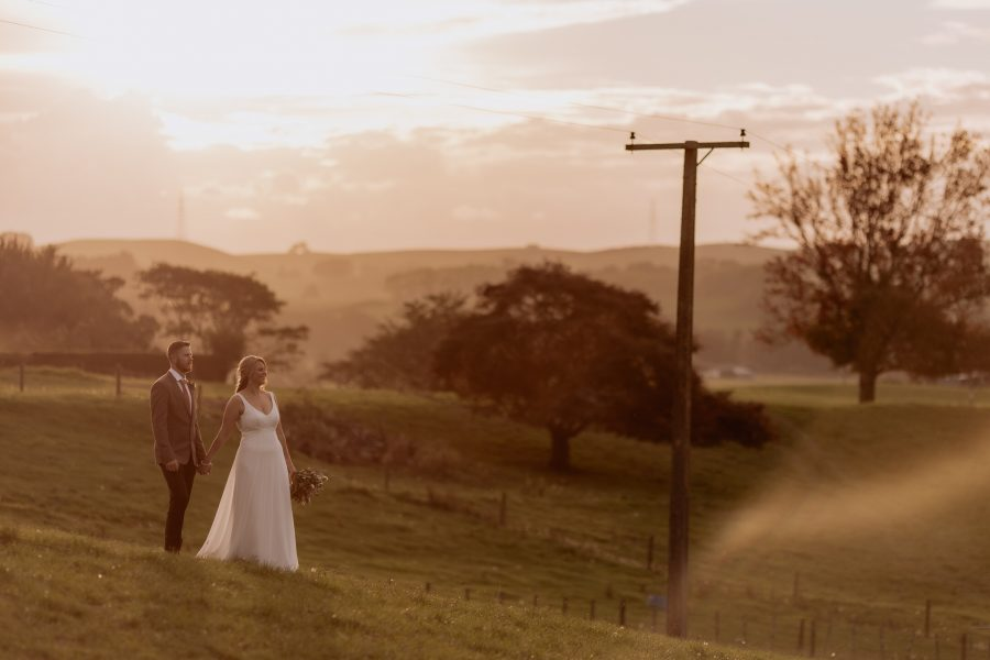 Bride and groom looking at kaimais country setting at sunset