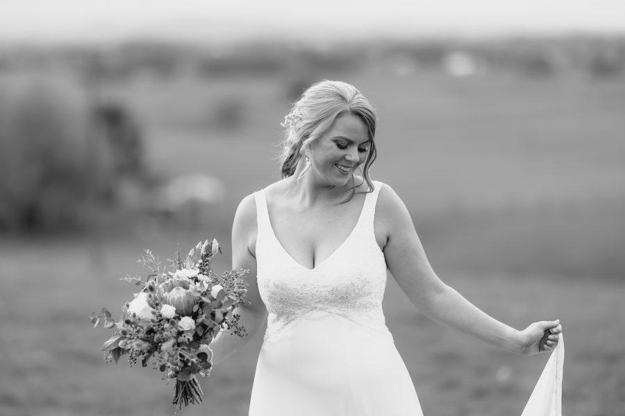 Bride walking naturally looking down at dress smiling