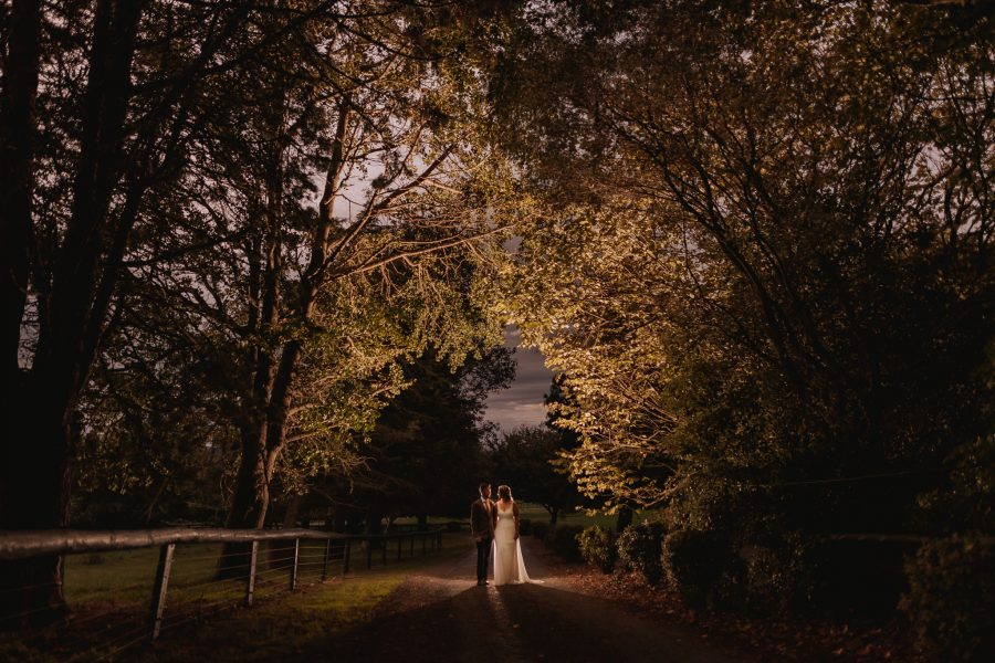 Autumn country back yard wedding bridal couple walking in driveway with trees lit up by flash