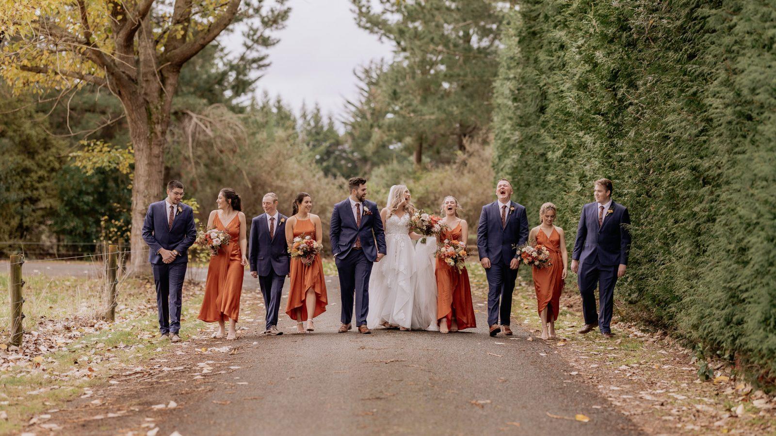 Makoura Lodge orange wedding party walking on driveway laughing