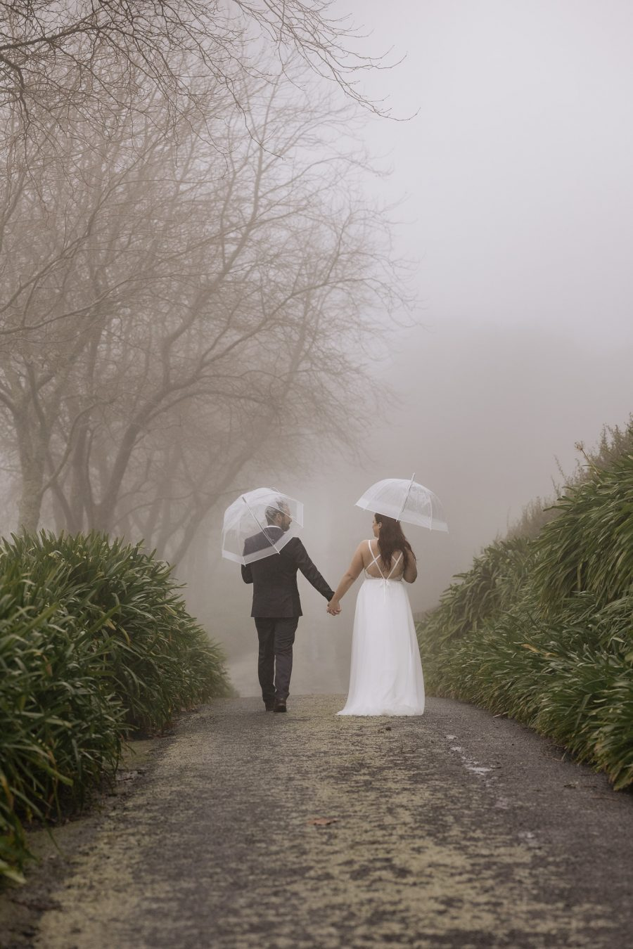 Bride and groom walking away holding hands on driveway in the rain and fog on a winter day