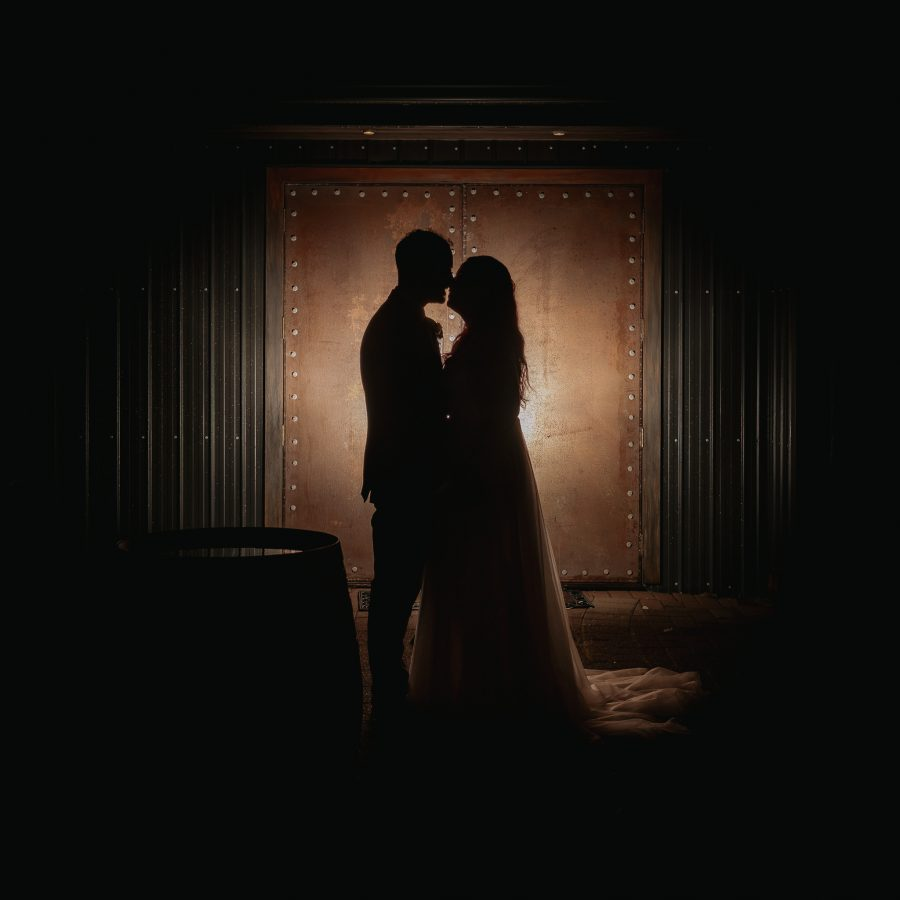 Bride and groom kissing in front of copper doors at Eagle Ridge estate