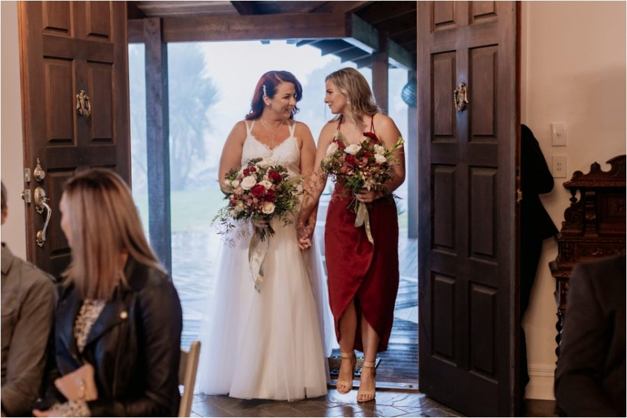 Bride arrives to aisle with bridesmaid