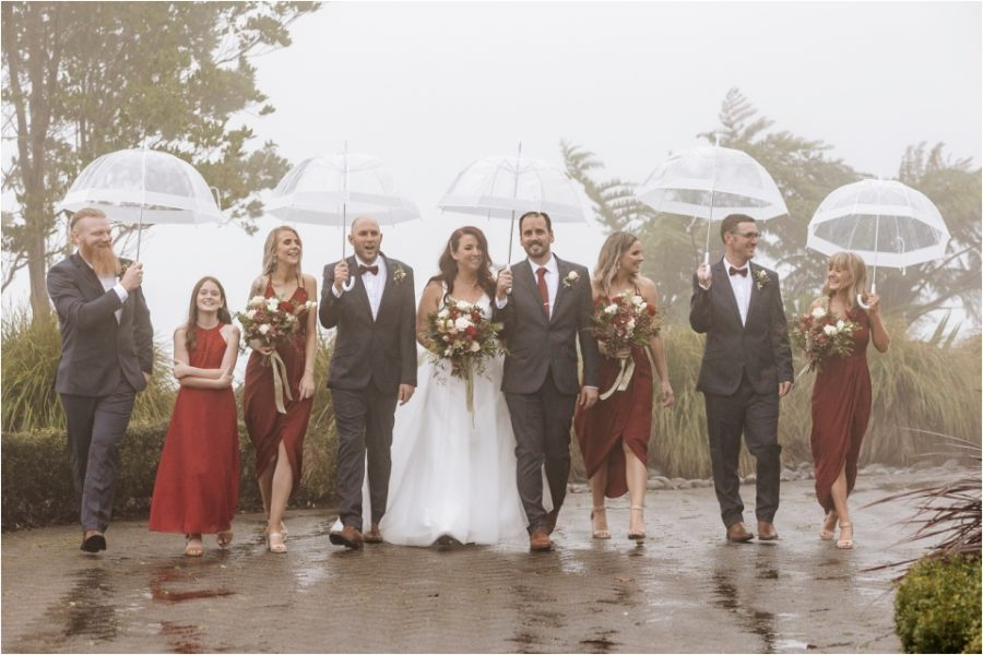 Bridal party walking in the rain with umbrellas