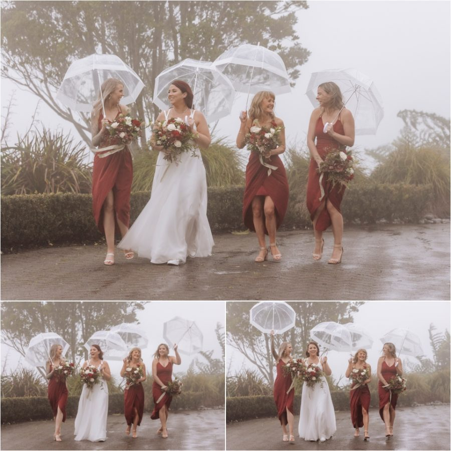 Laughing bridesmaids with bride with umbrellas laughing in the rain