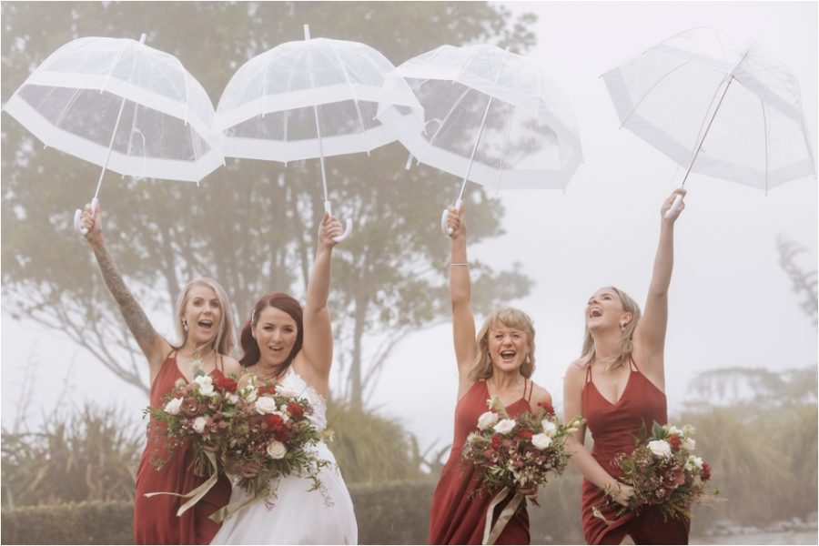 Party fun bride with bridesmaids holding up umbrellas in wine dresses.