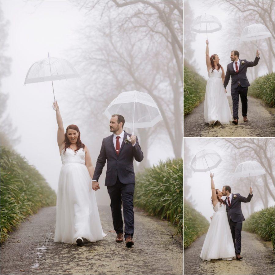 Celebrating wedding photos in the rain on driveway holding up umbrellas