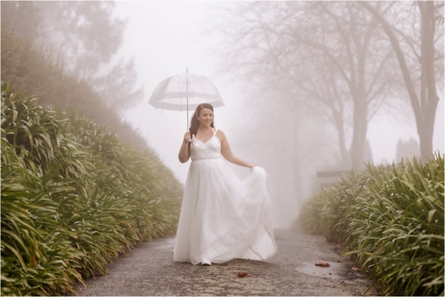 Bride walking on drive with umbrella in the clouds