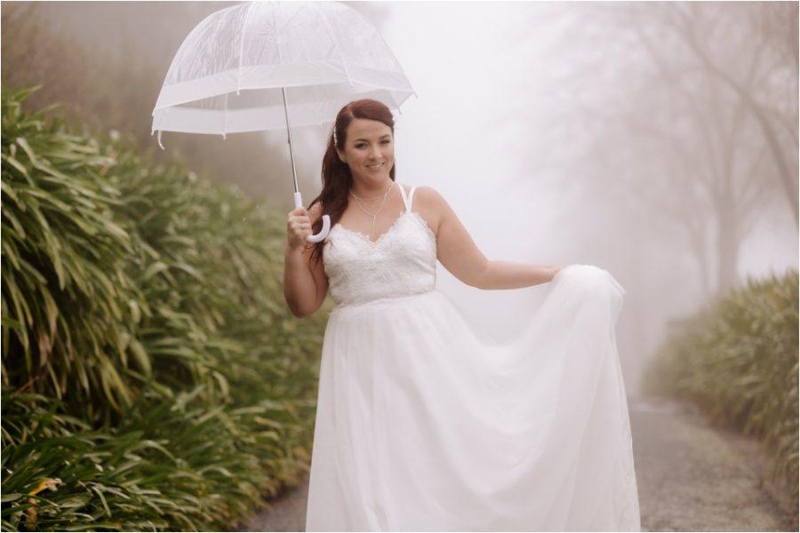 Happy bride walking in the rain