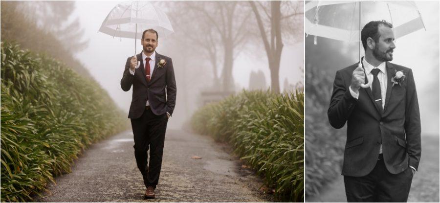Happy groom walking with umbrella in the rain