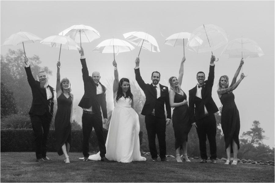 Fun happy photos wedding party holding up umbrellas